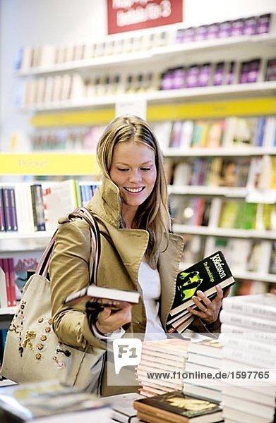 Eine junge Frau Blick auf Bücher in einem Buchladen Stockholm Schweden.