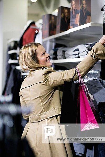 Frau mit Blick auf Kleidung Stockholm Schweden Einkaufstaschen.