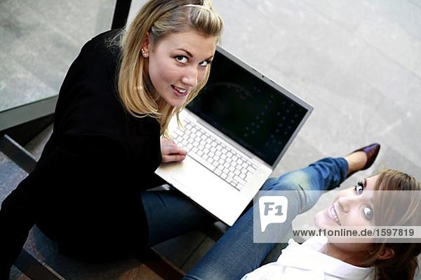 Zwei Frauen sitzen auf der Treppe mit einem Laptop.