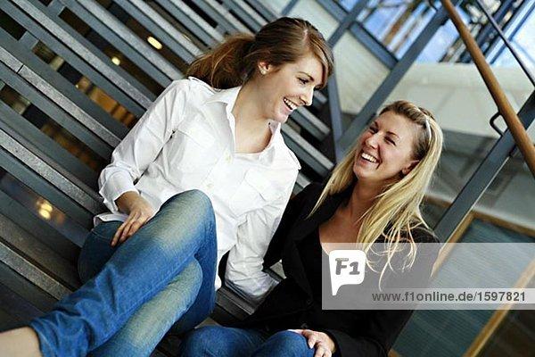 Zwei lächelnd Frauen sitzen auf der Treppe.