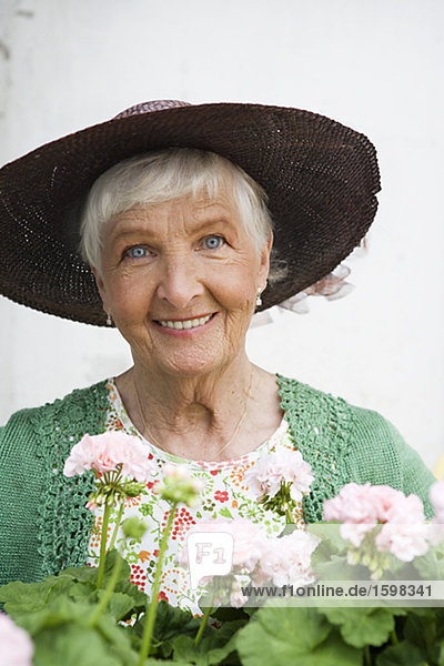 Alte skandinavische Frau mit Pelargonium Schweden.