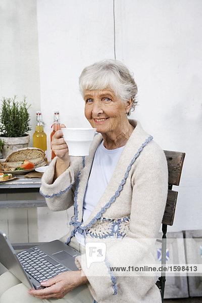 Eine ältere Frau Schreiben auf ihrem Computer und trinken eine Tasse Kaffee Schweden.