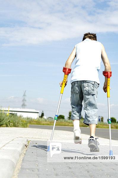 Rückansicht des jungen zu Fuß unterwegs mit gebrochenem Bein