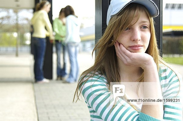 Close-up of teenage girl looking sad with her friends standing in background