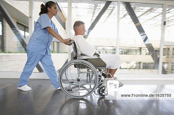 Krankenschwester stossend Patienten im Rollstuhl