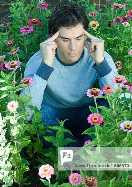 Man sitzt in Blumen  Augen geschlossen und die Hände auf Tempeln