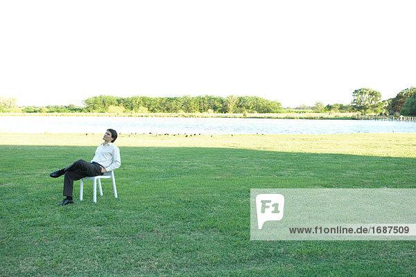 Businessman sitting in Stuhl auf Rasen  die Hände in Taschen  Blick nach oben