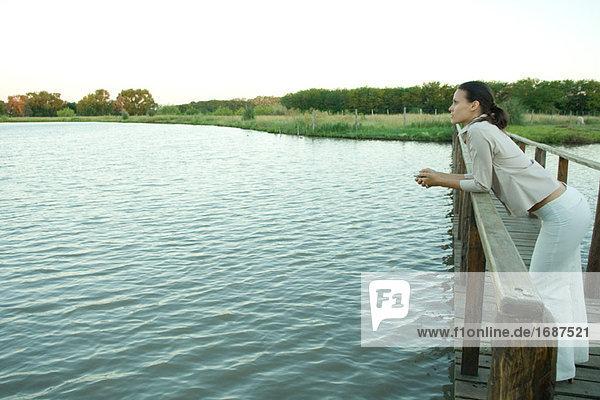 Frau stehend auf Holzsteg über See  in Ferne suchen