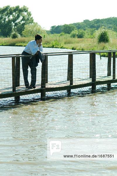 Kaufmann auf Holzsteg über See  Wegsehen