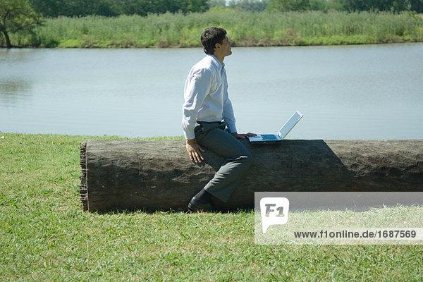 sitzend Notebook Geschäftsmann Baum Baumstamm Stamm wegsehen