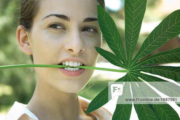Frau hält large Leaf in Mund  Wegsehen