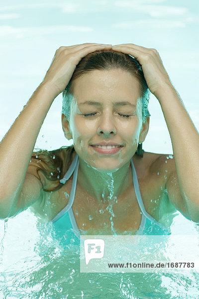 Junge Frau im Pool  plantschen Gesicht mit Wasser