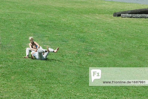 Couple sitting on grass together  man leaning back on woman