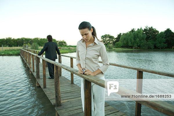 Mann und Frau stehend auf Fußgängerbrücke  Suchen von einander entfernt