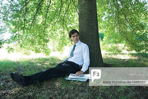 Kaufmann unter Baum sitzt