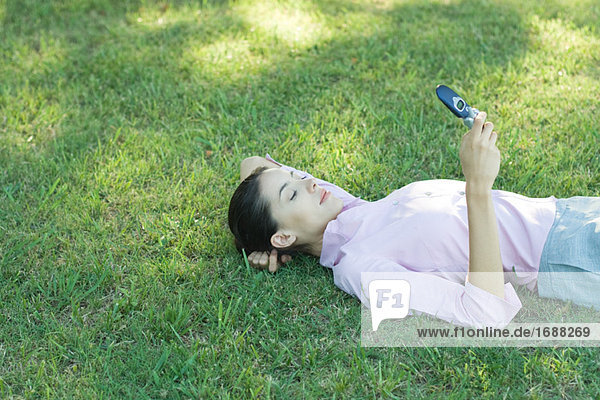 Geschäftsfrau liegen im Gras  Blick auf Handy