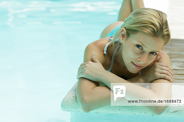 Junge Frau liegen am Rand des Pools  Blick in die Kamera