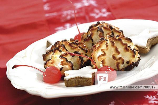 Kokosmakronen und sternförmige Zimtkekse auf einem Teller