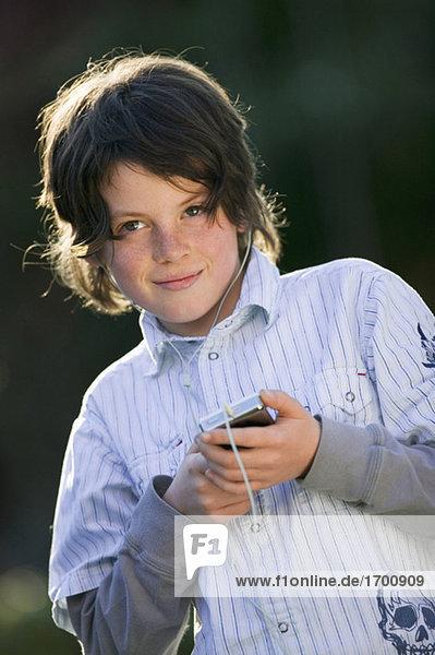 Boy (10-11) using mp3-player