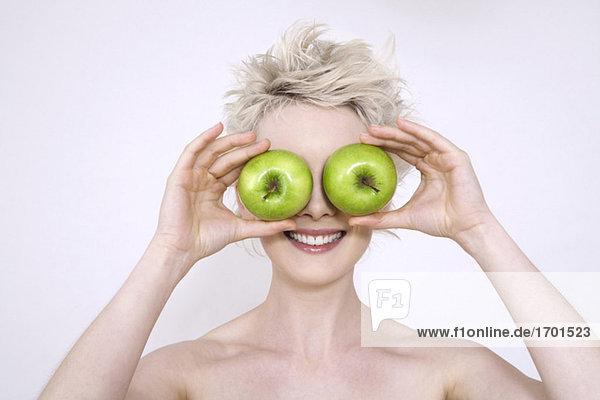 Junge Frau hält Äpfel über die Augen  Portrait