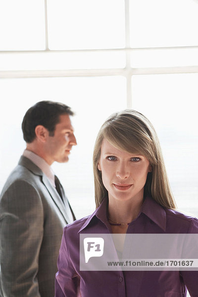 Portrait of business woman  male colleague in background