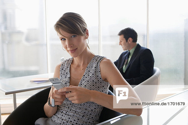 Business woman using mobile phone  male colleague in background