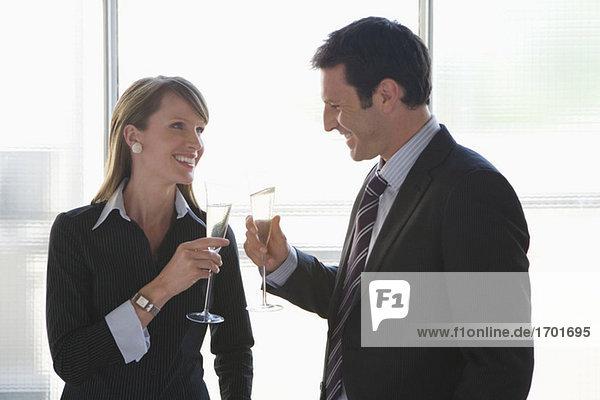Geschäftsfrau und Geschäftsmann toasten mit Sekt