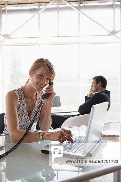 Business woman using laptop while phoning  male colleague in background