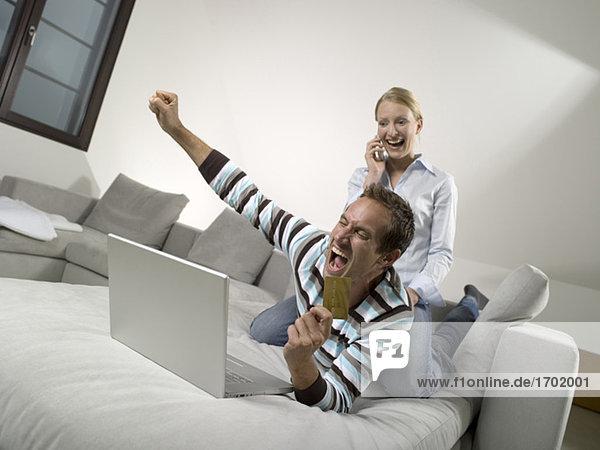 Paar auf Sofa  mit Laptop