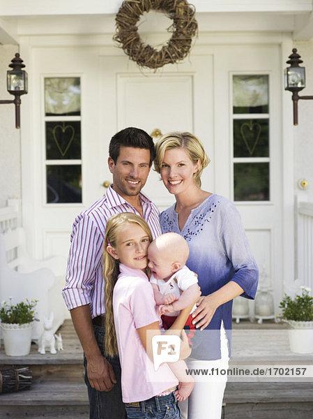 Familie mit Baby steht vor dem Haus