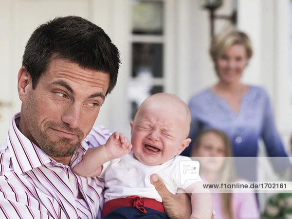 Familie mit Baby vor dem Haus