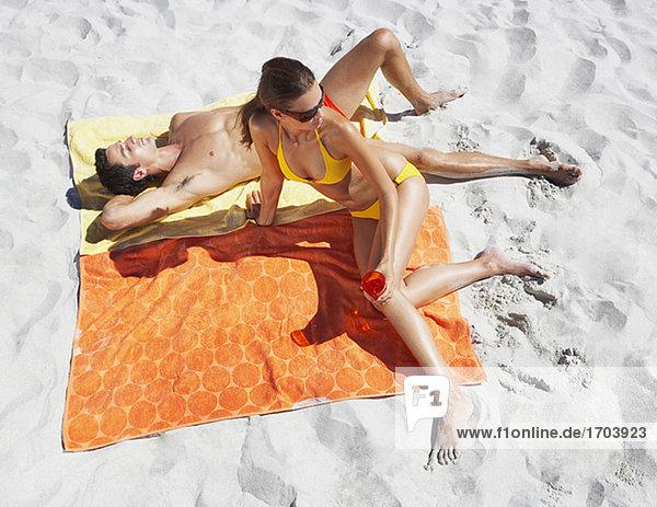 Mann und Frau Sonnenbaden am Strandtücher im sand