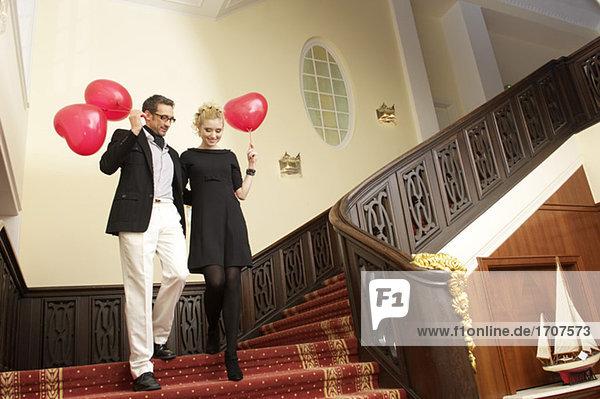 Paar mit herzförmigen Luftballons auf einer Treppe  fully_released