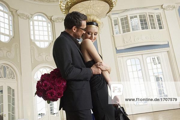 Mann mit einem Rosenstrauß umarmt eine Frau  fully_released