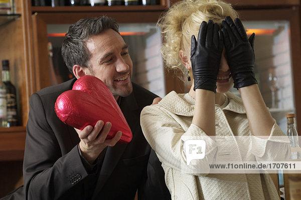 Mann überrascht Frau mit einem Pralinenherz  fully_released