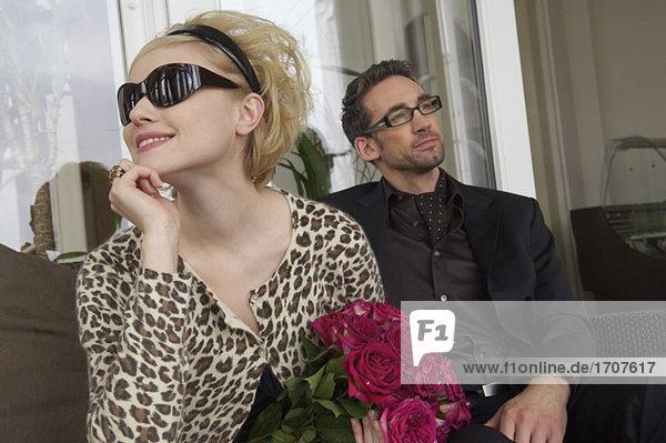 Paar sitzt nebeneinander  Frau hält einen Strauß Rosen  fully_released