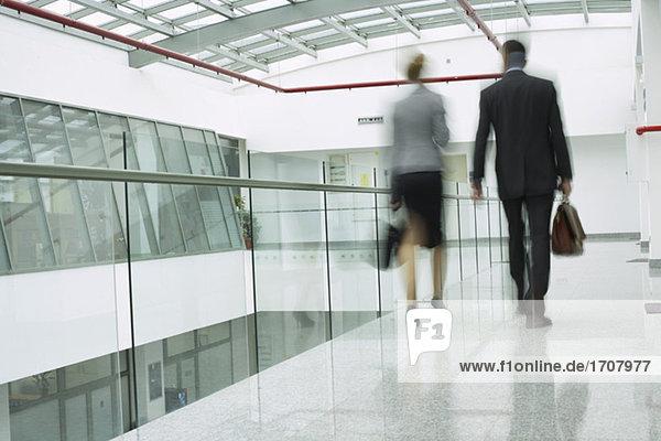 Zwei Geschäftsleute laufen über einen Korridor Zwei Geschäftsleute laufen über einen Korridor