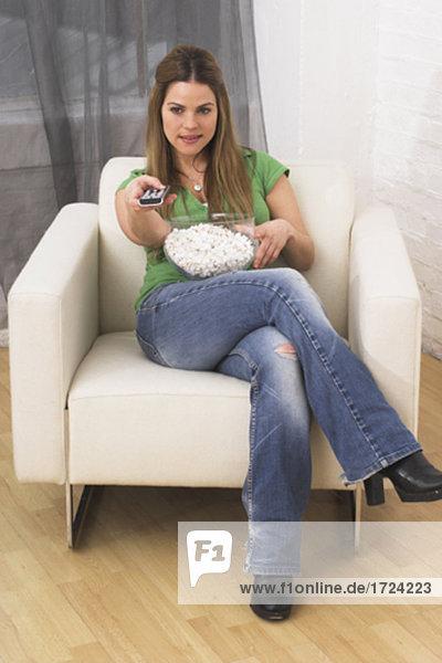 junge Frau vor dem Fernseher hält Fernbedienung und Essen popcorn