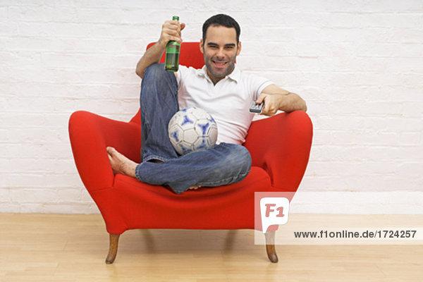 junger Mann in red Sessel halten  Fußball und Bier Flasche während vor dem Fernseher sitzen