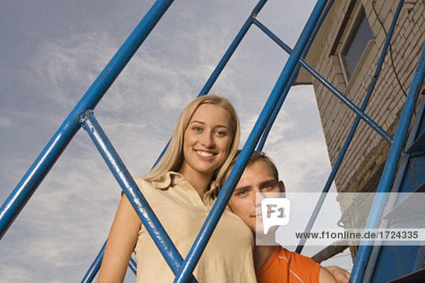 Portrait des jungen Paares durch Geländer schauen lächelnd