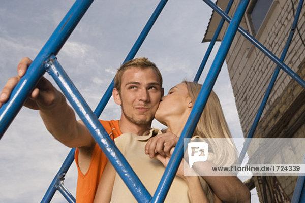 junges paar stehend auf Treppen Frau Mann auf Wange küssen
