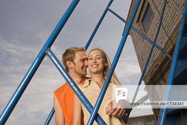 Portrait des jungen Paares auf Treppe lächelnd