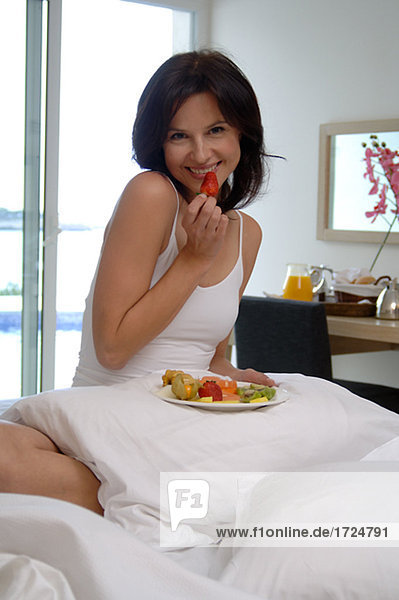 Woman in bed is eating fruits