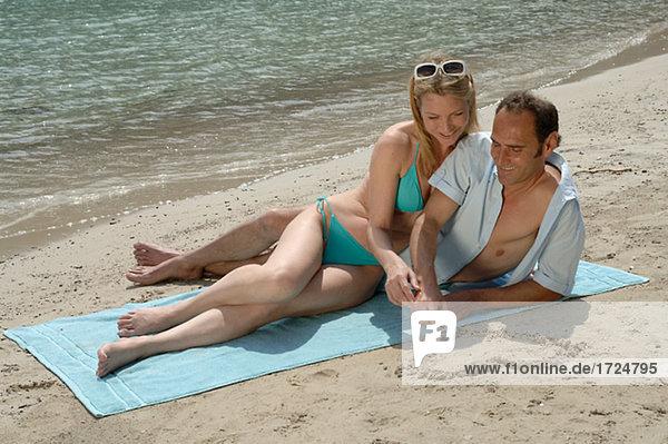 Mann malt ein Herz in den Sand