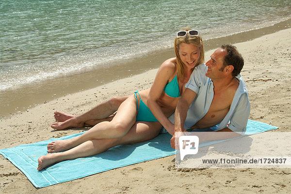 Paar liegt am Strand