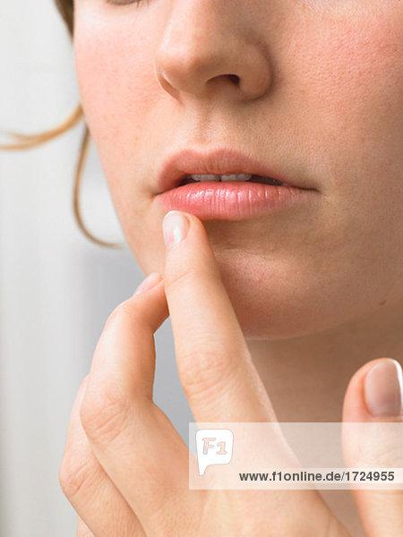 Frau fasst sich an die Lippe