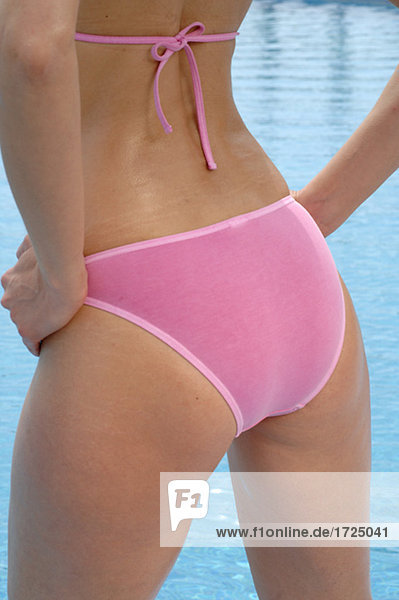 Lower part of the body of a woman in a pink bikini