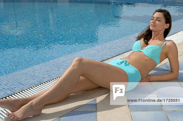 Woman at the swimming pool in a turquoise bikini