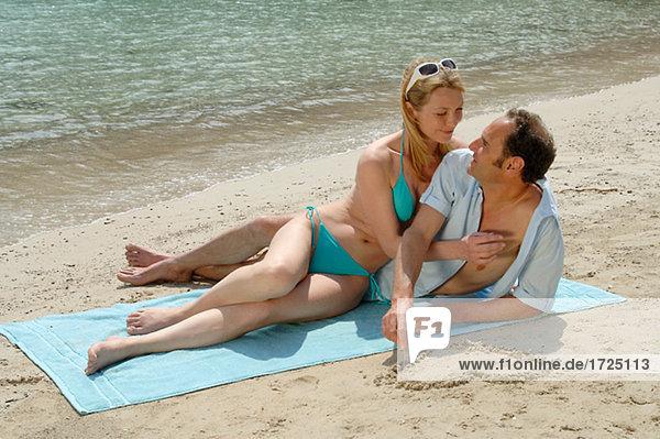 Paar am Strand auf einer Strandmatte