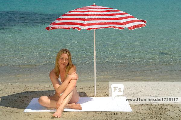 Woman sitting on the beach under a sunshade